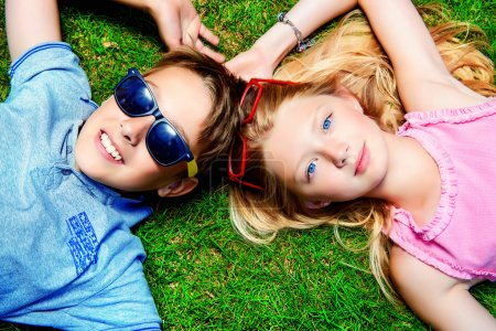 Photo for Two cheerful teenagers on the grass in the park. Summer. Friendship. - Royalty Free Image