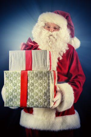 Photo for Portrait of Santa Claus holding gift boxes. Christmas time. - Royalty Free Image
