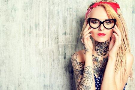 Photo pour Portrait en gros plan d'une jeune fille pin-up moderne portant une robe à pois à l'ancienne et des lunettes et des dreadlocks modernes. Coup de mode. tatouage . - image libre de droit