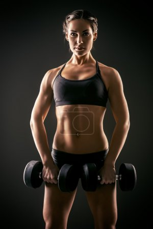 Photo for Slender young woman with beautiful athletic body doing exercises with dumbbells. Fitness, bodybuilding. Health care. - Royalty Free Image
