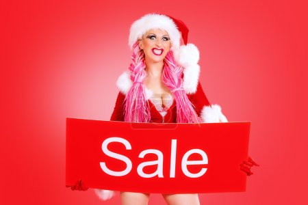 Photo for Sexual babe dressed as Santa Claus holding sale board. Red background. Christmas. - Royalty Free Image