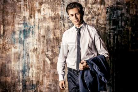 Photo for Portrait of a handsome young man in elegant suit standing over grunge background. - Royalty Free Image