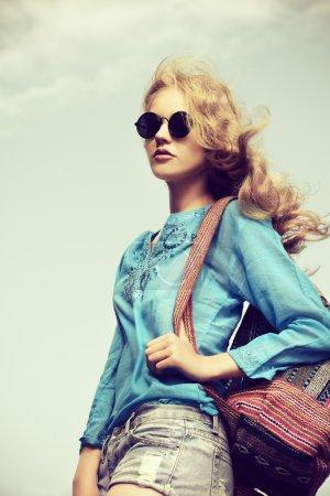 Photo pour Superbe jeune femme avec de beaux cheveux ondulés portant une blouse décontractée et un short en jean posant en plein air. Coup de mode . - image libre de droit