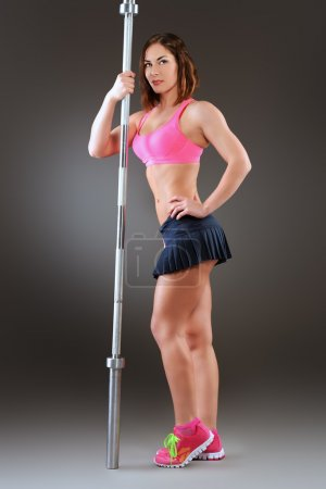 Photo for Beautiful young woman with athletic body posing with barbell. Fitness, bodybuilding. Health care. - Royalty Free Image