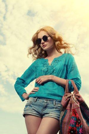 Foto de Hermosa joven con hermoso cabello ondulado con ocasionales shorts vaqueros y blusa posando al aire libre. moda tiro. - Imagen libre de derechos