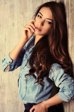 Photo pour Belle femme sensuelle en jeans se tient près du mur grunge. Mode . - image libre de droit