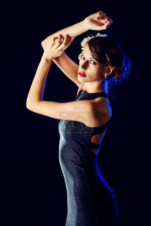 Photo for Glamorous young woman wearing black evening dress posing over black background. Luxury. Beauty, fashion. Make-up. - Royalty Free Image