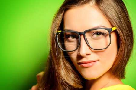 Photo for Beauty portrait of a positive young woman in spectacles and bright yellow dress over green background. Beauty, fashion. Optics. - Royalty Free Image