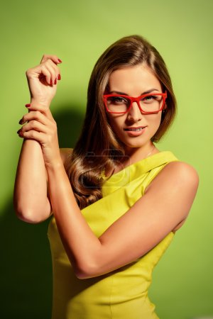 Photo pour Beauty portrait of a positive young woman in spectacles and bright yellow dress over green background. Beauty, fashion. Optics. - image libre de droit