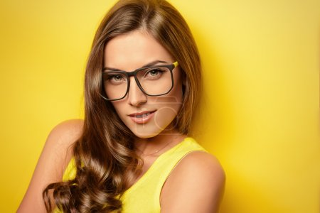 Photo for Beauty portrait of a happy young woman in spectacles and bright yellow dress over yellow background. Beauty, fashion. Optics. - Royalty Free Image