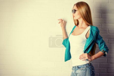 Photo pour Superbe jeune femme posant devant le mur de briques blanches. style de jeans. beauté, mode. - image libre de droit