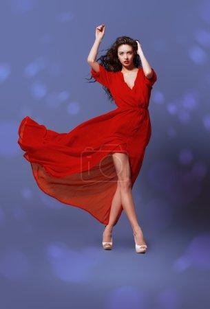 Photo pour Coup de mode de la femme élégante en belle longue robe posant en mouvement. Studio shot. - image libre de droit
