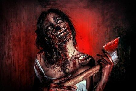 Foto de Chica zombie sangriento miedo con un hacha. Halloween. - Imagen libre de derechos