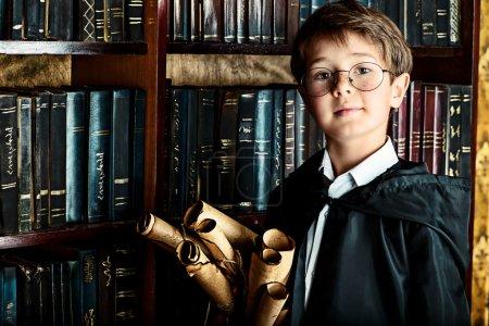 Foto de Un niño se encuentra en la biblioteca por los estantes con muchos libros antiguos y posee manuscritos antiguos. Concepto educativo. Ciencia. Estilo vintage. - Imagen libre de derechos