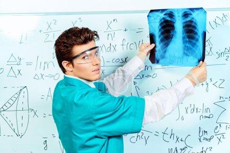 Photo pour Un chirurgien examine la radiographie de la poitrine d'un patient. Soins de santé, médecine . - image libre de droit