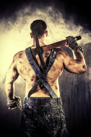 Photo for Masculine dirty coal miner with a pickaxe over dark grunge background. Mining industry. Strength. Bodybuilding. - Royalty Free Image