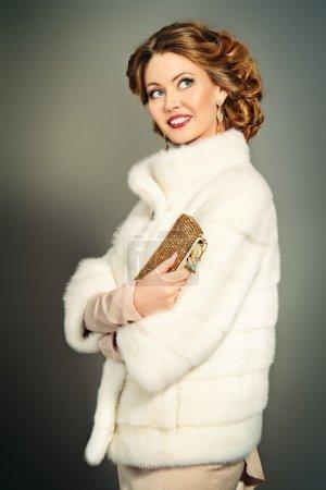 Foto de Concepto de belleza, moda y lujo. Elegante joven con maquillaje de noche y peinado posando en el hermoso vestido y blanca chaqueta de piel de visón. Joyería. Estudio tiro. - Imagen libre de derechos