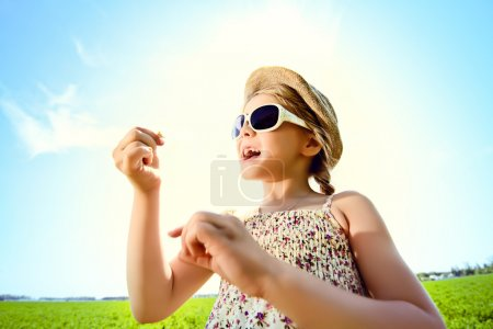 Photo for Pretty little girl blows bubbles on a meadow in summer day. Happy childhood. Blue sky. - Royalty Free Image