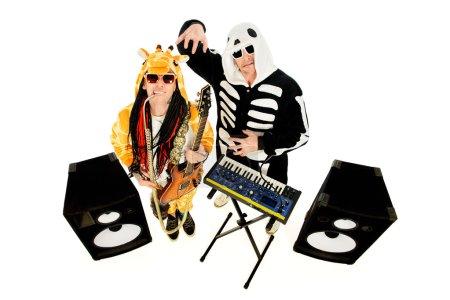Photo pour Rock band en costumes de squelette et girafe jouant du synthétiseur et de la guitare électrique et chantant. Spectacle musical. Halloween. Isolé sur blanc . - image libre de droit