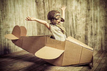 Photo for Cute dreamer boy playing with a cardboard airplane. Childhood. Fantasy, imagination. Retro style. - Royalty Free Image