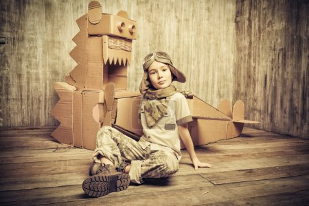 Photo for Cute dreamer boy playing with a cardboard airplane and dinosaur. Childhood. Fantasy, imagination. Retro style. - Royalty Free Image
