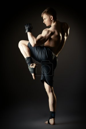Photo for Man in sportswear performing a kick. Martial arts. Studio shot. - Royalty Free Image