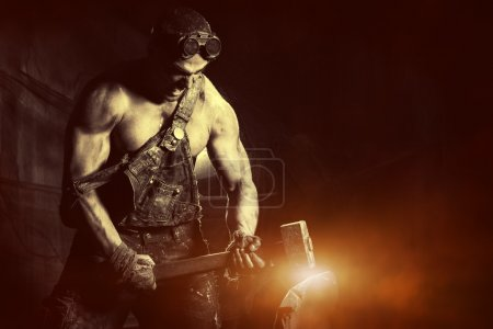 Rage muscular coal miner working with a hammer ove...