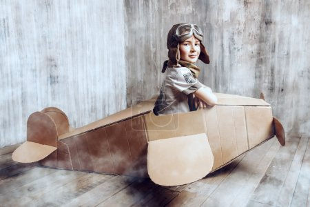 Photo for Little dreamer boy playing with a cardboard airplane. Childhood. Fantasy, imagination. - Royalty Free Image