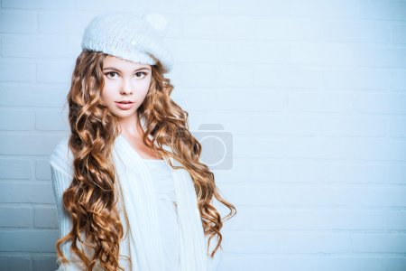 Photo for Cute teenager girl with beautiful long curly hair wears white knitted jersey and beret. Beauty, fashion. - Royalty Free Image