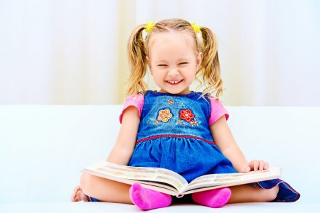 Photo for Pretty little girl sitting on a sofa and looking at a children's picture book. Happy childhood. - Royalty Free Image