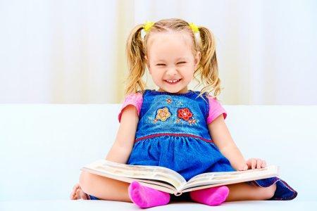 Photo pour Jolie petite fille assise sur un canapé et regardant un livre d'images pour enfants. Bonne enfance . - image libre de droit