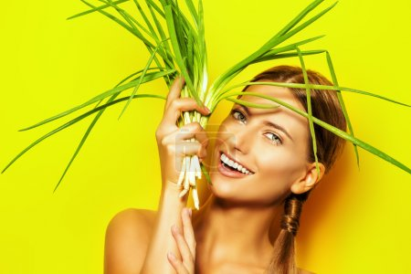 Photo for Joyful young woman with green onion over summer yellow background. Healthy food. - Royalty Free Image
