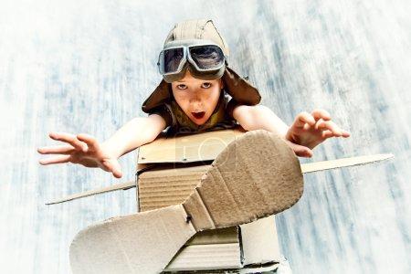 Photo pour Petit rêveur jouant avec un avion en carton. Enfance. Fantaisie, imagination . - image libre de droit
