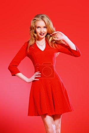 Photo pour Charmante souriante jeune femme en robe rouge et avec blonde bouclés cheveux. beauté, mode. cosmétiques, maquillage. fond rouge. - image libre de droit