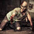 Horrible scary zombie man on the ruins of an old h...