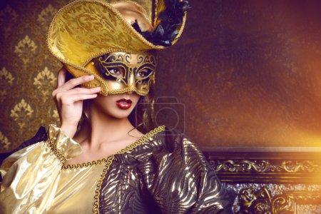 Photo pour Carnaval masqué vénitien. Élégante dame portant une belle robe luxuriante et un masque vénitien se tient dans une salle du palais. Renaissance. Barocco. Mode . - image libre de droit