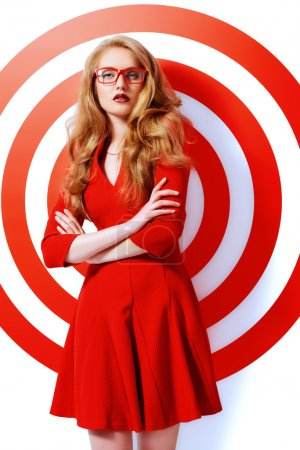 Photo for Gorgeous fashion model in red dress and elegant red glasses posing over red circles of the target. Beauty, fashion. Optics, eyewear. - Royalty Free Image