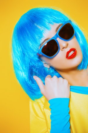 Photo for Bright glamorous girl in vivid clothes and a wig alluring over yellow background. Beauty, fashion. Cosmetics, hairtsyle. Optics, eyewear. - Royalty Free Image