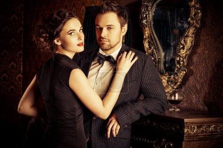 Photo pour Bel homme et femme dans des vêtements de soirée élégants dans des appartements vintage classiques. Glamour, mode. Concept d'amour . - image libre de droit