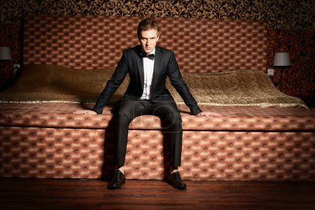 Photo for Handsome man in elegant suit sitting on a bed. Luxury. Vintage interior. - Royalty Free Image