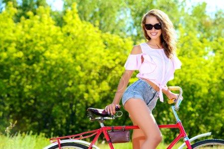 Photo pour Bonne fille en vélo dans le parc un jour d'été. Vacances d'été . - image libre de droit