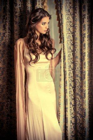 Photo pour Jolie femme brune en robe de soirée magnifique posant par les tentures vintage. Beauté, mode . - image libre de droit
