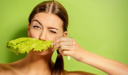 Photo for Pretty cheerful young woman posing with fresh green lettuce leaves. Healthy eating concept. Dieting. - Royalty Free Image