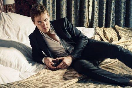 Photo pour Attrayant beau homme en costume élégant, couché sur un lit avec verre de boisson. Luxe. Vintage interior. - image libre de droit