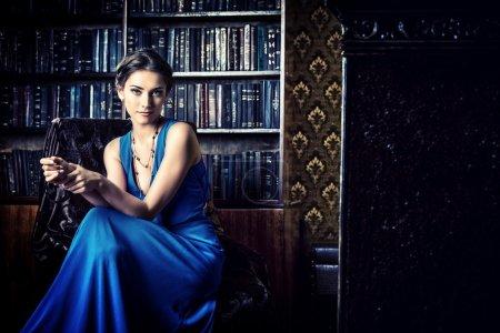 Photo pour Élégante dame portant une robe de soirée assise sur la chaise dans la vieille bibliothèque vintage. Beauté, mode . - image libre de droit