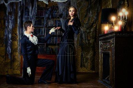 Photo pour Beaux vampires hommes et femmes vêtus de vêtements médiévaux se tiennent dans une pièce de l'ancien château abandonné. Halloween . - image libre de droit