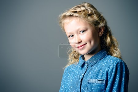 Photo for Pretty smiling eight-year girl in jeans dress posing at studio. Kid's beauty, fashion. - Royalty Free Image