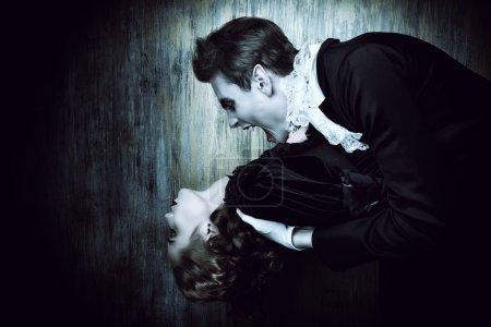 Photo pour Sanguinaire vampire mâle en robe médiévale se mord une belle dame. Halloween. - image libre de droit