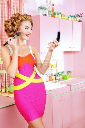 Pretty woman doing makeup on her glamorous pink ki...