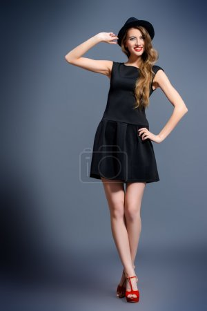 Photo for Joyful pretty girl wearing black dress and black classic hat posing at studio. Full length portrait.  Beauty, fashion concept. Hipster style. - Royalty Free Image